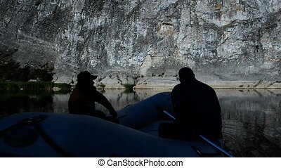 Silhouettes of tourists in a boat on the water against the...