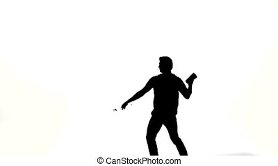 Young bartender does a trick with a shaker. silhouette -...