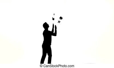 silhouette of barman man showing tricks with a bottle on...