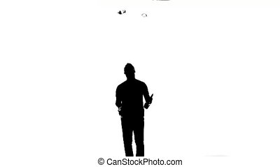 silhouette of barman showing tricks with a bottle -...