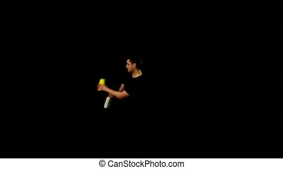 Young bartender with a shaker and bottle on black background
