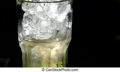 A cube of ice falling into a glass of water close up slow...