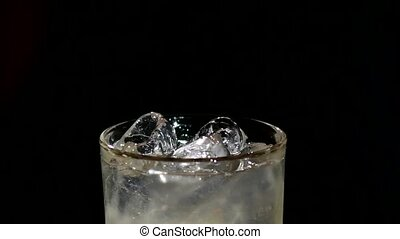 A cube of ice falling into a glass of water on black. close up. slow motion