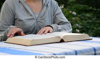 Woman reading a book in a garden