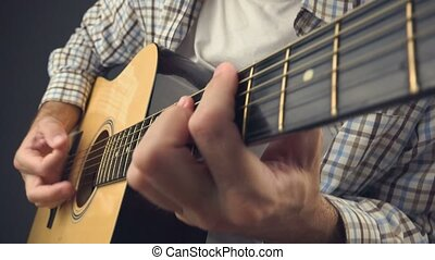 Musician playing rock tune on acoustic guitar, unplugged...