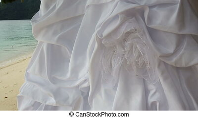 closeup of white wedding dress hangs on green tree - closeup...