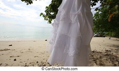 white wedding dress hangs on island - white wedding dress...