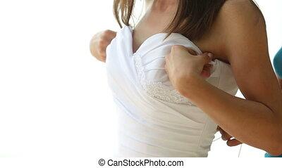 assistant helps bride tie corset of wedding dress on beach -...