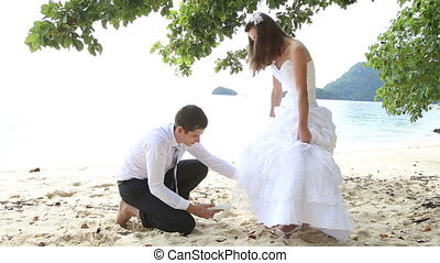 groom puts shoe on long haired bride under tree on beach -...