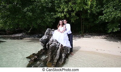 handsome groom embraces brunette bride sitting on rock