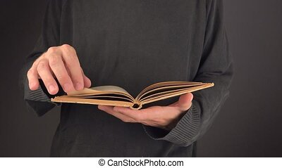 Man turning pages of old book