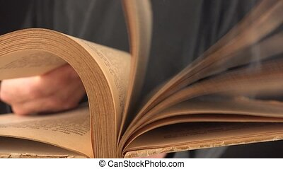 Man turning pages of old book - Man turning yellow pages of...
