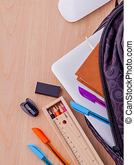 Backpack with school supplies laptop,book stationary,mouse,pen,ruler, and color pencil on wooden table .