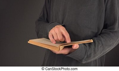 Man searching text in vintage book - Man searching text and...