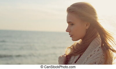 Charming woman with long hair wearing a knitted cardigan stands at the sea and thinking at sunset