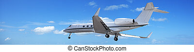 Private jet maneuvering in a blue sky. Panoramic...