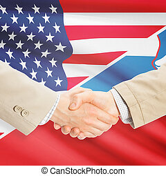 Businessmen handshake - United States and Slovenia -...