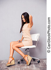 Woman sitting on office chair with backpain - Portrait of a...