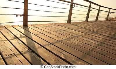 young sports woman running on seaside wooden boardwalk