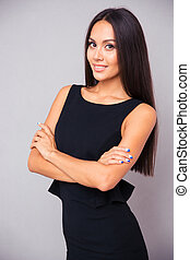 Smiling businesswoman standing with arms folded