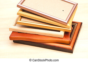 Stack of picture frames isolated on a wooden background