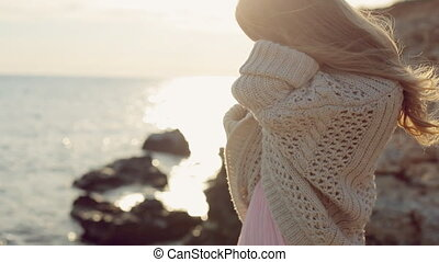 Sensual blond girl wearing a cardigan near the sea at sunset...