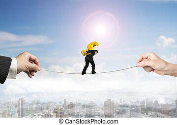Businessman carrying dollar sign balancing tightrope with...