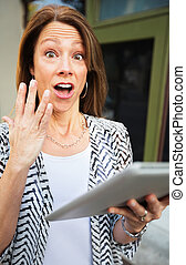 Startled Woman with Tablet Computer - Startled mature adult...