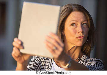 Woman Puckering Lips at Tablet - Conceited European female...