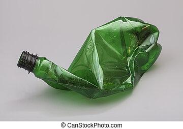 Crushed plastic bottle isolated on gray background