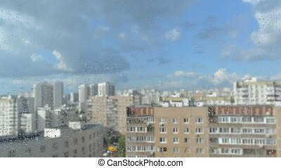 Drops of rain on a window pane, buildings in background....