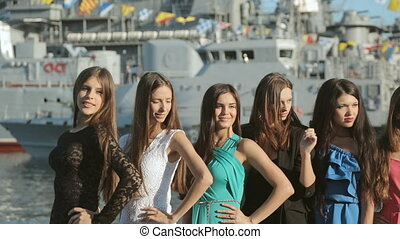 Group of beautiful models posing on the background of a warship near the sea