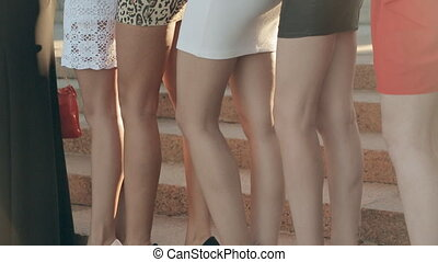 Slender girls clothed in short dress posing near the columns