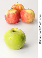 Green and Red Apples - Fresh Green apple in front of 3 red...