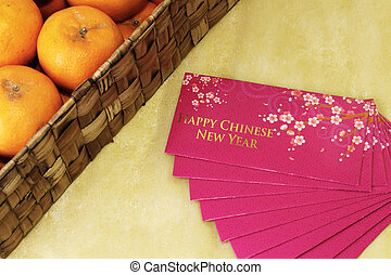 Chinese New Year money packets with a box of Mandarin...