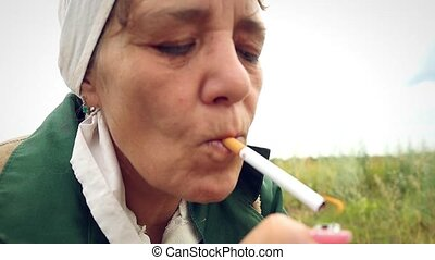 aged woman smoking a cigarette in a scarf on the nature and coughs