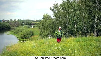 Mature beautiful smiles woman in scarf with birch brooms on the forest glade