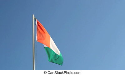Request Ivory Coast flag in front of blue sky