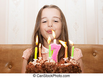 little girl blowing out the candles - little girl 7 years...