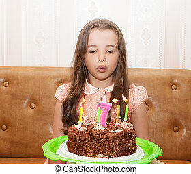 little girl blowing out the candles on a birthday cake -...