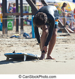 Surfer wears safety leash to the ankle on the beach