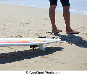 Surfer with longboard on the beach - Close up of legs of a...