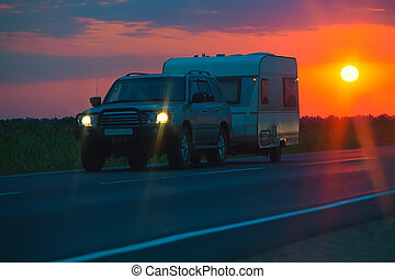 SUV with the tourist trailer at sunrise