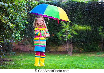 Little girl playing in the rain under colorful umbrella -...
