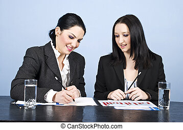 Two business women writing in office
