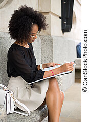 business woman - young woman in the city writing in her...