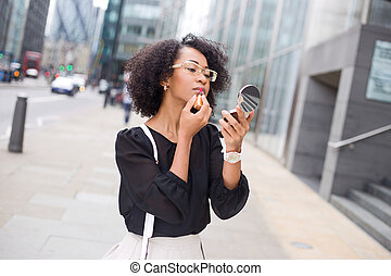 makeup - business woman apllying lipstick in the street