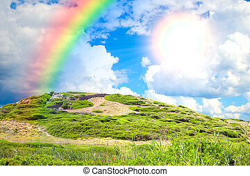 Summertime green hill background with bright sun and rainbow.