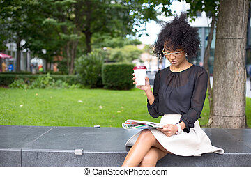 coffee break - young woman enjoying a coffee and reading a...