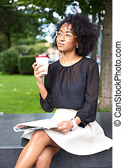 coffee break - young woman holding a magazine and coffee